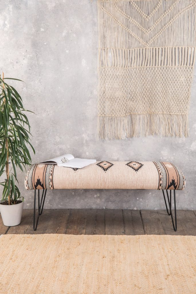 Cream wooden long bench with metal legs that works well as a window seat