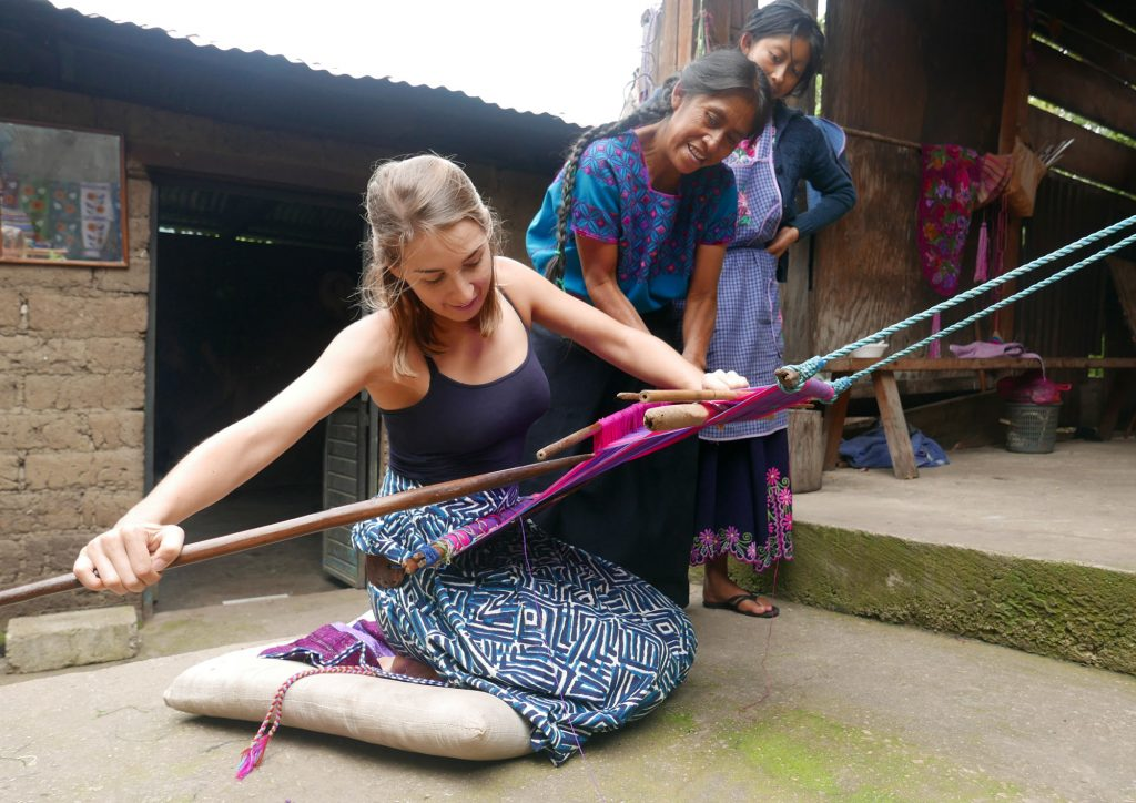 Olivia from the Nido Collective trying backstrap weaving
