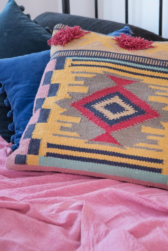 Use this Aztec design cushion to support the maximalism home trend