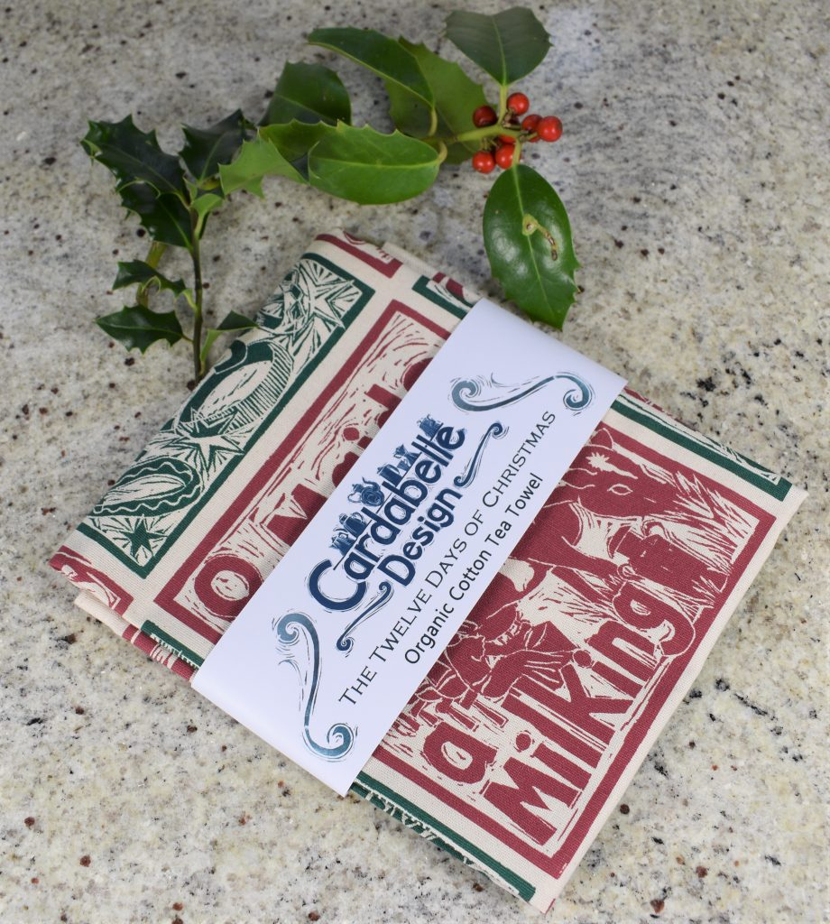 Festive tea towel designed from lino cuts by Kate Guy