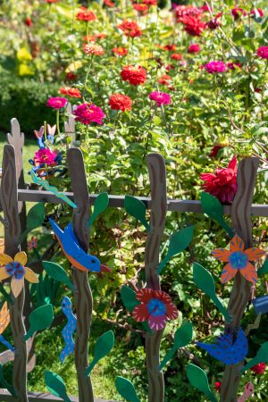 Colourfully and artistically decorated fence next to a flower garden